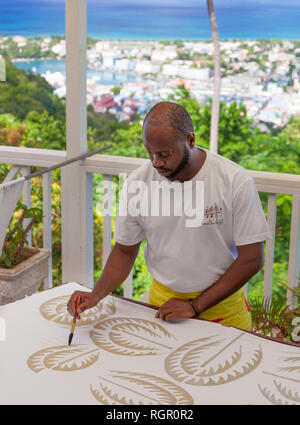 Man making Batik cloth by painting wax into the desired design. Howelton Estate, Saint Lucia, Caribbean. - Stock Image