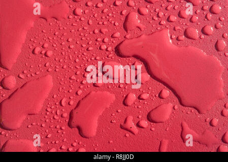Multiple water drops raindrops on red background - Stock Image