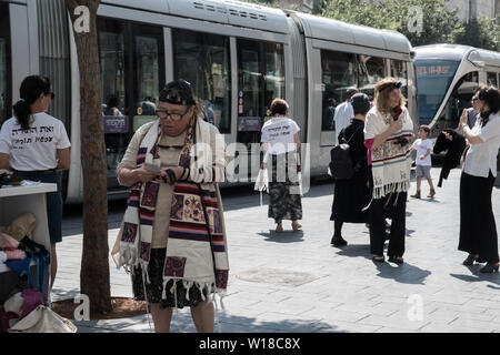 Jerusalem, Israel. 1st July, 2019. Women of the Wall, an organization known for fighting for women's prayer rights at the Western Wall, runs a tefillin, or phylacteries, wrap stand for women in Jerusalem's down town. Municipal approval for the move was received after repeated appeals over several months. Tefillin, two small black boxes containing parchment with verses from the Hebrew Bible are wound around the head and the arm with black leather straps and are considered a commandment in Orthodox Judaism. As such they are traditionally men's domain only. Credit: Nir Alon/Alamy Live News. - Stock Image