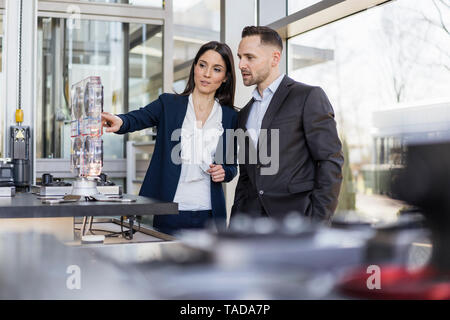 Businessman and businesswoman talking at a machine in modern factory - Stock Image
