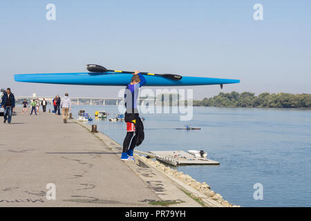 Young man carrying a kayak on the Danube River in Zemun. Belgrade, Serbia. - Stock Image