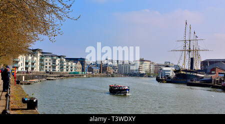 Bristol floating harbour quayside with modern apartment building on left, SS Great Britain on right and ferry going through docks - Stock Image