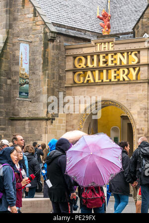 Holyrood, Edinburgh, Scotland, United Kingdom, 12th August 2018. UK Weather: the rain and mist as the remnants of Storm Debby hits the capital does not deter tourists at Holyrood Palace. People queuing to at the Queen's Gallery holding umbrellas - Stock Image