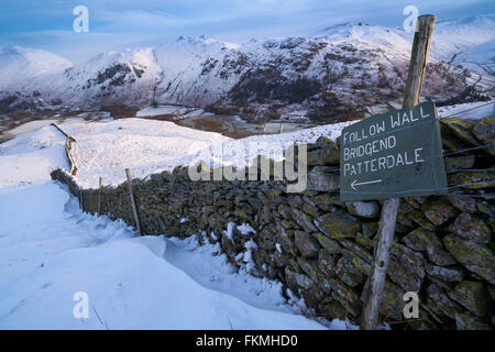 Signpost by a stone wall pointing towards Bridgend, Patterdale in the English Lake District. - Stock Image