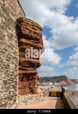 Overhanging cliff of soft red sandstone at Sidmouth, Devon. - Stock Image