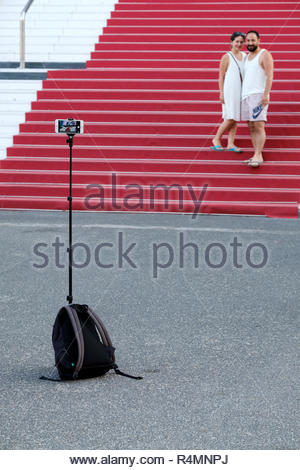 A couple pose for a selfie on the red carpet outside of the  Palais des Festivals et des Congrès in cannes, France. The phone is mounted on a tripod - Stock Image