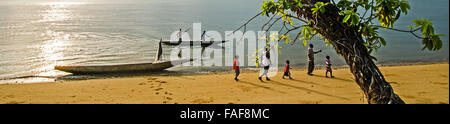 Villagers walk along a beach on Sei Island, the Turtle Islands, Sierra Leone. - Stock Image