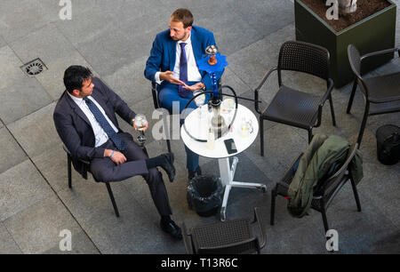 Two businessmen in suits having a drink after work in Seville - Stock Image