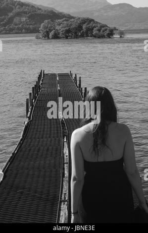 Loch Lomond, Scotland.  Woman walks out onto a lake boat jetty in the high heat of British Summer.  Black and White. - Stock Image