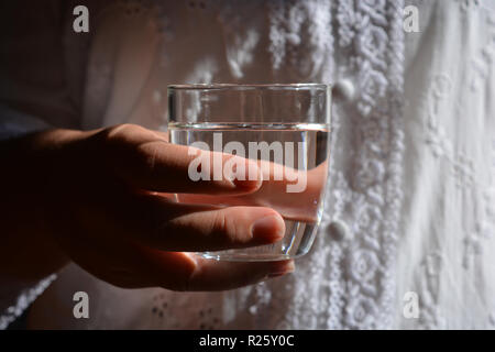 Woman holding a glass of water - Stock Image