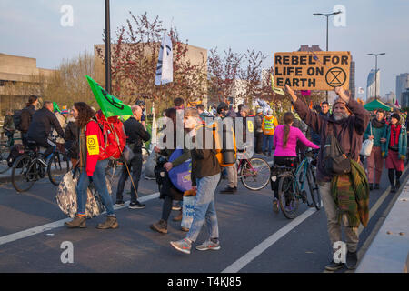 A protestor marches across Waterloo Bridge for the Extinction Rebellion demonstration with a placard 'Rebel for Life on Earth' - Stock Image