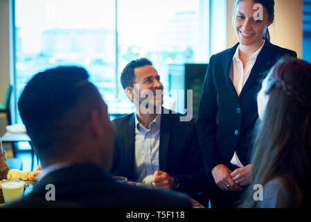 Waitress taking order from business people at bar - Stock Image