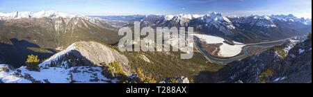 Wide Panoramic Landscape of Snowcapped Mountain Peaks and Bow River Valley in Alberta Foothills of Canadian Rockies near Banff National Park - Stock Image