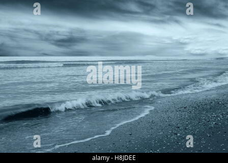 deserted sea with dramatic cloudy sky - Stock Image