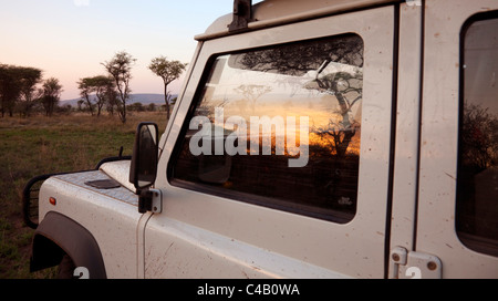 Tanzania, Serengeti. Sunrise over the bush is reflected in the window of a Land Rover. - Stock Image