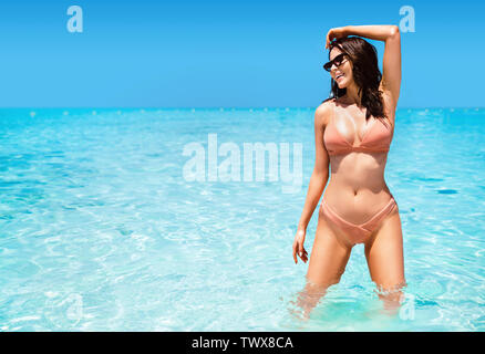 Portrait of a sensual woman posing in a clear, ocean water - Stock Image