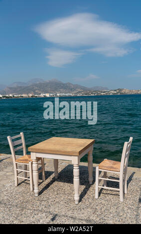 Ierapetra, Crete, Greece. June 2019. Empty chairs and table on the quayside of this southern Crete resort. - Stock Image