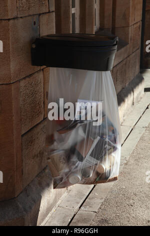 Rubbish in a polythene bag on a platform at Oxenholme station - Stock Image