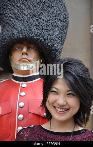 Japanese tourist posing beside model of soldier wearing a bearskin cap, Cambridge, England, UK - Stock Image