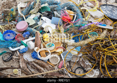 Trash collected on coastal beach. - Stock Image