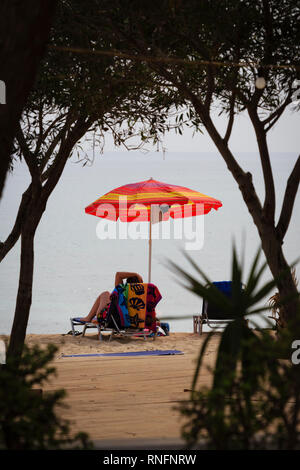 Woman on a lounger on the beach at Potamos, Cyprus October 2018 - Stock Image