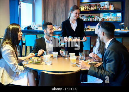 Waitress serving food to business people in bar - Stock Image