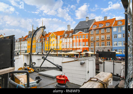The colorful historical buildings along the Nyhavn canal rise above the deck of a docked sailboat in Copenhagen Denmark - Stock Image