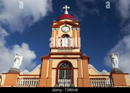 Spanish Church Facade Building Exterior with Cross Shape, Tower Clock and Statues of Angels Colonial Architecture San Jose Costa Rica City Center - Stock Image