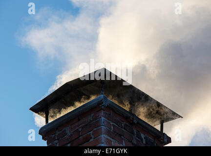 Smoke from smokestack , heating the house with firewood - Stock Image