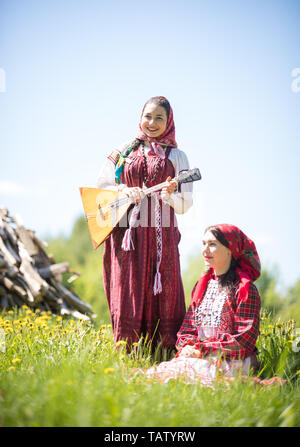Two young women in traditional russian clothes are in the field, one of them is sitting - vertical shot - Stock Image