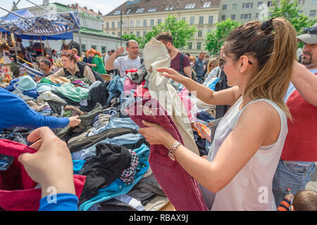 Flea market Vienna, view of people sorting through a popular clothes stall in the Naschmarkt - the famous open-air market in Vienna, Wien, Austria. - Stock Image