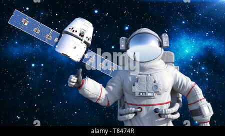 Astronaut with satellite showing thumbs up, cosmonaut floating in space with spacecraft in the background, 3D rendering - Stock Image