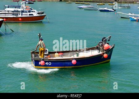 Fisherman on a small fishing boat in St Ives Harbour,Cornwall,England,UK - Stock Image