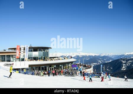 Kronplatz, South Tyrol, Italy - February 15, 2019: people enjoy skiing and sunbathing at Kronplatz Plan de Corones ski resort in the snowy Dolomites o - Stock Image