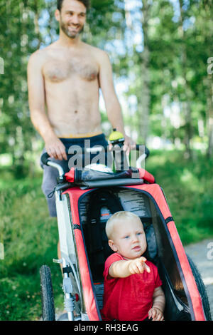 Father with son in jogging pram - Stock Image