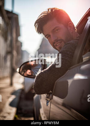 Handsome man sitting in his car looking at camera - Stock Image
