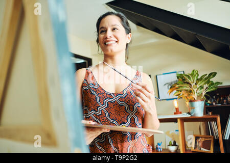 Portrait of hispanic young woman painting in her home studio, exercising with paint, brush, easel and color for hobby. - Stock Image