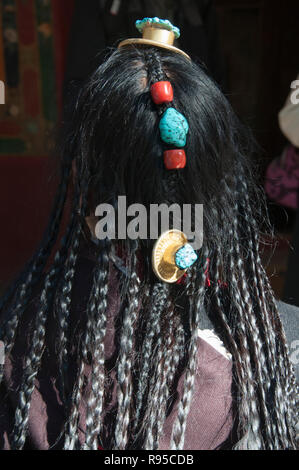 Woman displaying her hair adornments and jewellery on an outing to the Norbulingka Summer Palace, Lhasa, Tibet, China - Stock Image