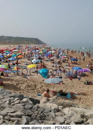 Lourinha, Portugal. 5 August 2018. beach in Praia da Areia Branca Lourinha Portugal busy already on another hot day in Portugal. Lourinha is 1 hour north of Lisbon on the Silver Coast. people flock to the cool of the Atlantic Ocean whilst the country experiences record temperatures. the region is also on high fire alert. Credit: EDimages/Alamy Live News - Stock Image