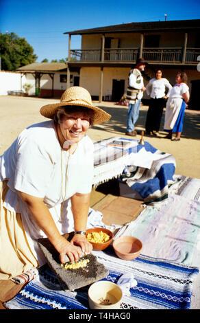 California Ventura Olivas Adobe Historic Park working ranchero metate corn grinder guide in costume - Stock Image