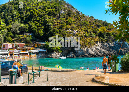 A young couple on a motorcycle arrive at a small bay near Palaiokastritsa Beach on the Greek island of Corfu. - Stock Image