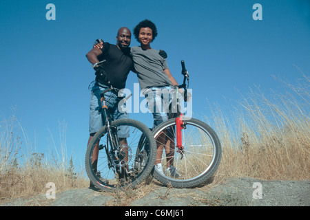 African American father and son with mountain bikes - Stock Image