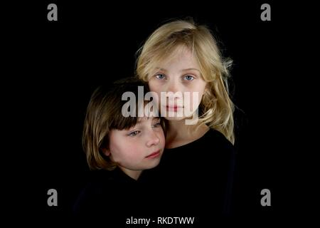 Closeup of two young sisters grieving and holding each other against a black background - Stock Image