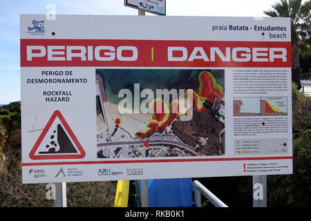 Danger Sign Warning Tourists About Falling Rocks On The Beach At Lagos Portugal - Stock Image