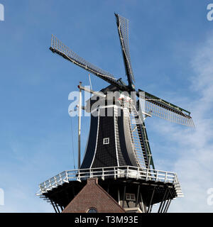 The Molen de Adriaan (Adriaan Windmill) in Haarlem, the Netherlands. The mill is illuminated by sunshine and stands against a blue sky. - Stock Image