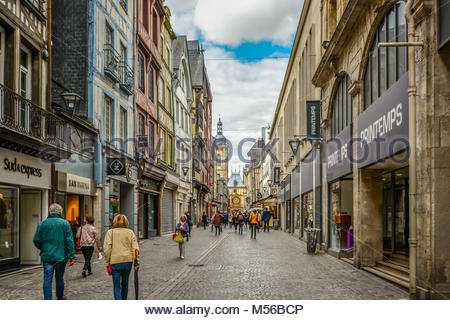 Tourists enjoy a stroll along the shops on the Rue du Gros Orloge in Rouen France with the astronomical clock in - Stock Image