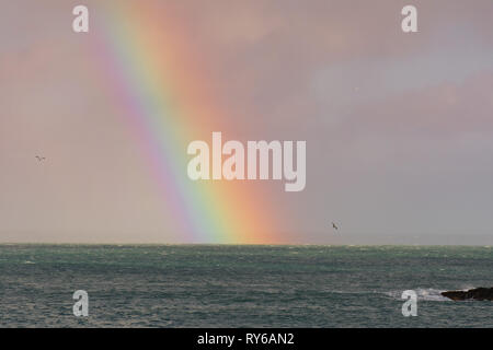 Mousehole, Cornwall, UK. 12th Mar, 2019. UK Weather. Heavy showers out at sea result in a colourful rainbow for residents of Mousehole. Credit: Simon Maycock/Alamy Live News - Stock Image