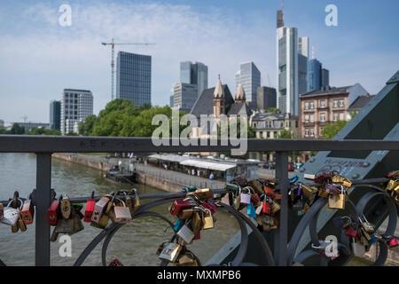 Love padlocks left on Eiserner Steg bridge, with city skyline in the background, Frankfurt am Main, Hesse, Germany. - Stock Image