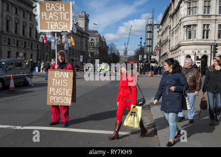 On the occasion of Commonwealth Day, a woman carrying a plastic bag walks past an environmental activist standing in Parliament Square, advocating the ban on plastics around the world, on 11th March 2019, in Westminster, London, England. - Stock Image