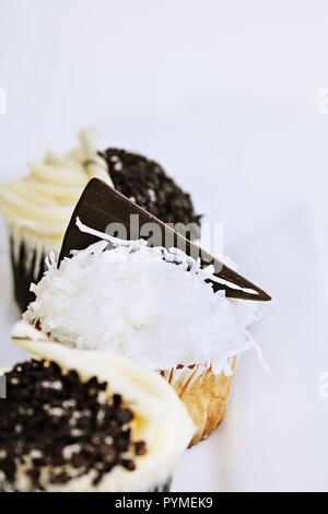 Pretty coconut frosted cupcake decorated with a wedge of dark chocolate. Extreme shallow depth of field with selective focus on center cupcake. - Stock Image